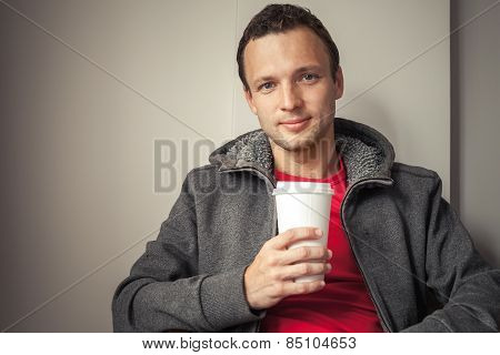 Portrait of young Caucasian man in hoodie sitting in cafe with paper cup of Coffee poster
