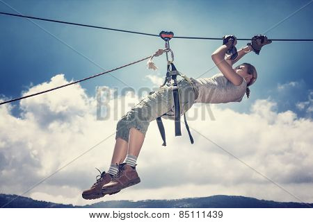Active sportive woman hanging on the tightrope between mountains, playing rappel sport, extreme lifestyle, great sportive achievement