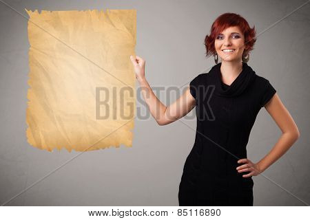 Beautiful young girl presenting old paper copy space