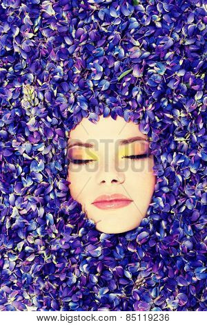 Beutiful young woman with colorful makeup and violet flowers of lupin.