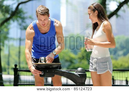 Public park water fountain couple runners drinking. Two young active male and female adults thirsty after run using a drinking fountain in Central Park, New York City, Manhattan in summer, USA.