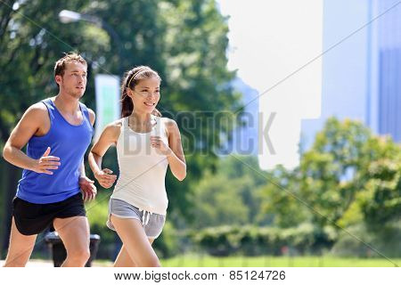 Runners jogging in New York City Central Park, USA. Healthy couple of new yorkers athletes running in summer sun working out a cardio exercise on Manhattan, United Sates of America.
