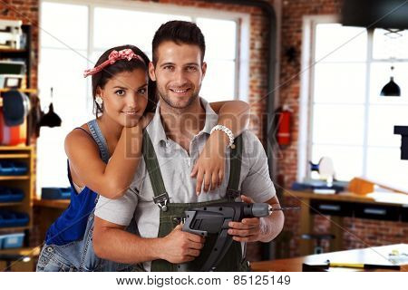 Happy young caucasian couple standing at home workshop, looking at camera, hugging, smiling. Power drill in hand.