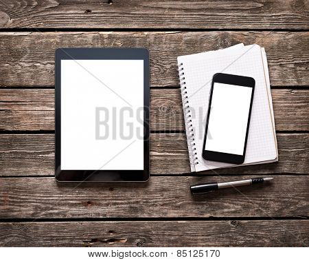 Digital tablet with phablet and notepad on desktop. Clipping paths included.