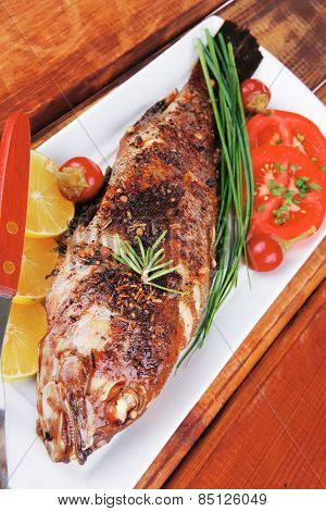 savory on wood: whole fried sunfish over plate with tomatoes lemons and peppers