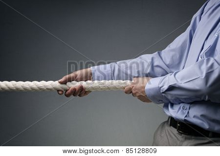Businessmen pulling tug of war with a rope concept for business competition, rivalry, challenge or dispute