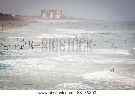 JUNO BEACH, FL - APRIL 20, 2013: Swimmers and surfers enjoy the ocean waves and warm weather at Juno Beach, Florida.