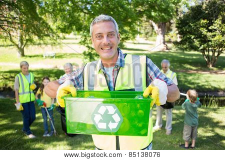 Happy father holding recycling case on a sunny day
