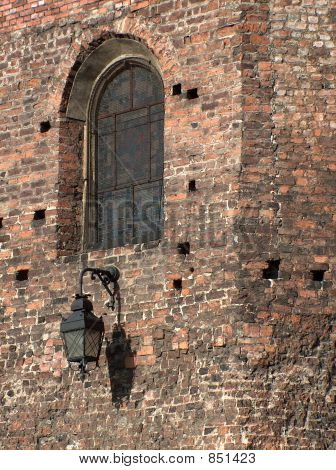Historical lantern attached to a brick medieval wall