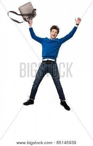 Laughing business man jumping with bag over white background