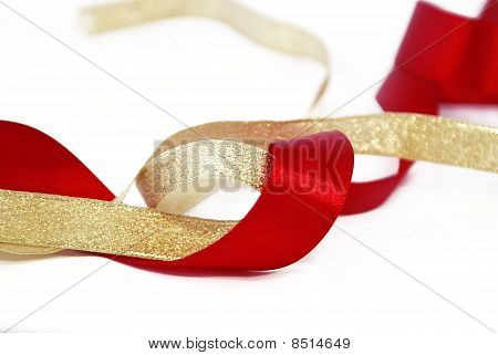 Ribbons: Red Satin And Goldish On A White Background.