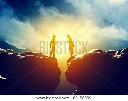 Two men handshake over mountains precipice. Business, deal, connection concepts