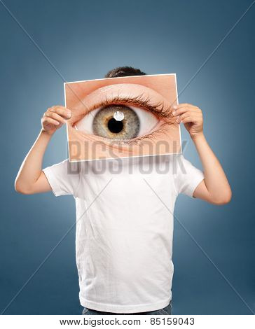 kid holding a picture of an eye watching