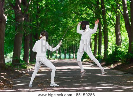Two rapier fencer women fighting over park alley, attacking each other in jumping