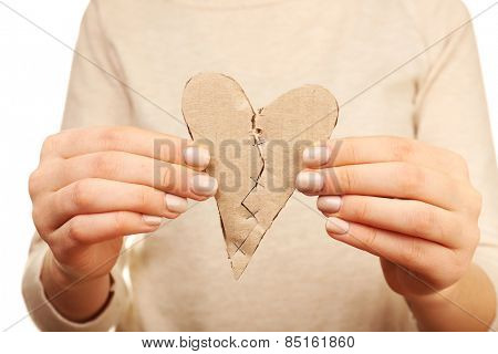 Woman holding broken heart stitched with staples close up