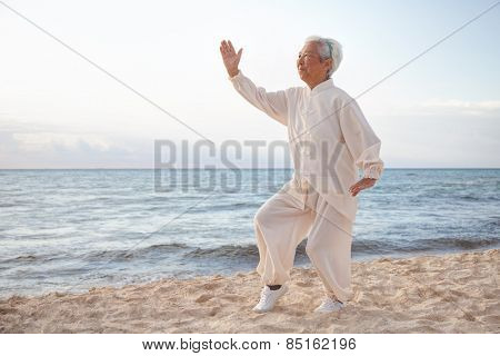 Chinese Elderly Woman Performing Taichi Outdoor by the beach under sunset sunrise