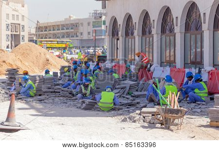 DOHA, QATAR - MARCH 8, 2015: Asian labourers at work removing a paved area from Souq Waqif, a popular tourist destination in Doha