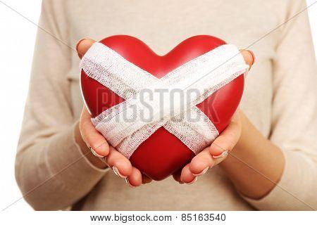 Woman holding bandaged heart close up