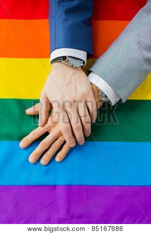 people, homosexuality, same-sex marriage, gay and love concept - close up of happy male gay couple hands over rainbow flag