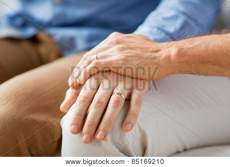 people, homosexuality, same-sex marriage, gay and love concept - close up of happy male gay couple holding hands with wedding rings on