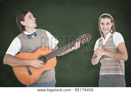 Geeky hipster serenading his girlfriend with guitar against green chalkboard