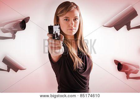 Femme fatale pointing gun at camera against cctv camera