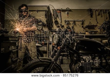 Mechanic doing lathe works in motorcycle customs garage  poster