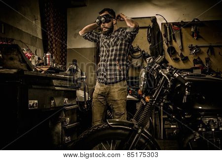 Mechanic preparing ford lathe works in motorcycle customs garage  poster
