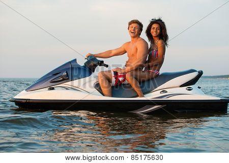 Multi ethnic couple sitting on a jet ski poster