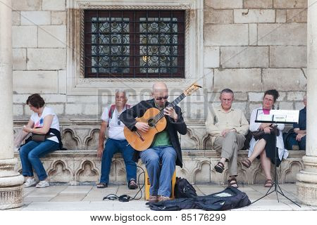 DUBROVNIK, CROATIA - MAY 26, 2014: Street guitar player  performing on Stradun.  Stradun is 300 meters long main pedestrian street in Dubrovnik.