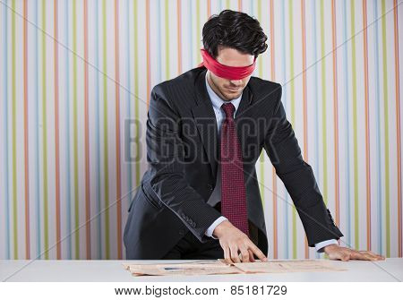 Blindfold businessman reading the newspaper