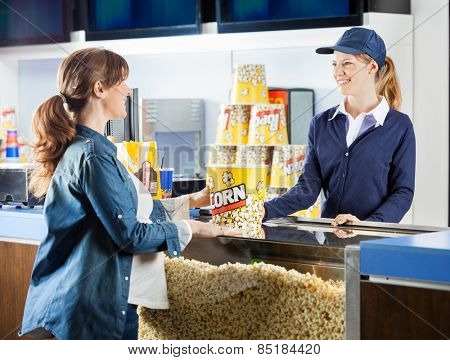 Mid adult pregnant woman buying popcorn from seller at cinema concession stand