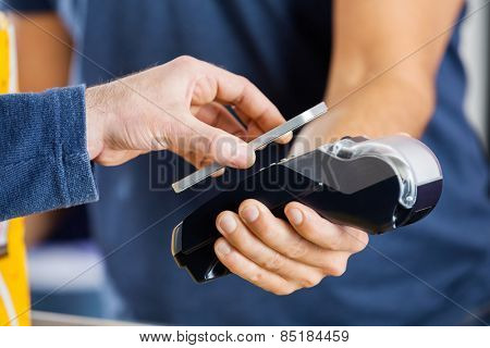 Cropped image of man paying through smartphone using NFC technology at cinema