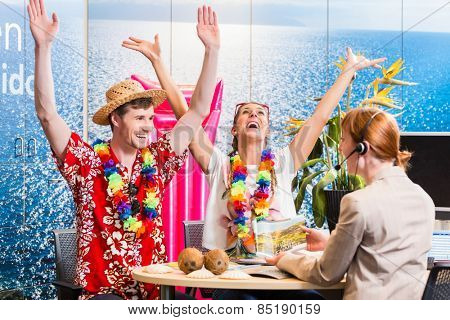 Man and woman booking vacation in travel agency cheering for a good deal poster