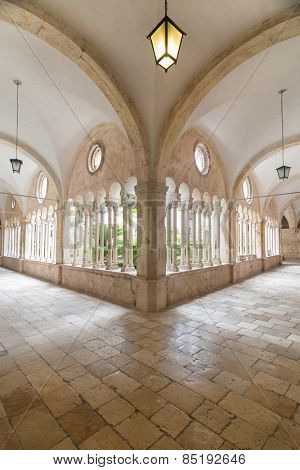 Hallway around famous courtyard in the Monastery of the Friars minor in Dubrovnik, Croatia.