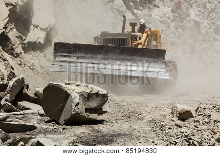 Bulldozer cleaning landslide from road in Himalayas. Himachal Pradesh, India