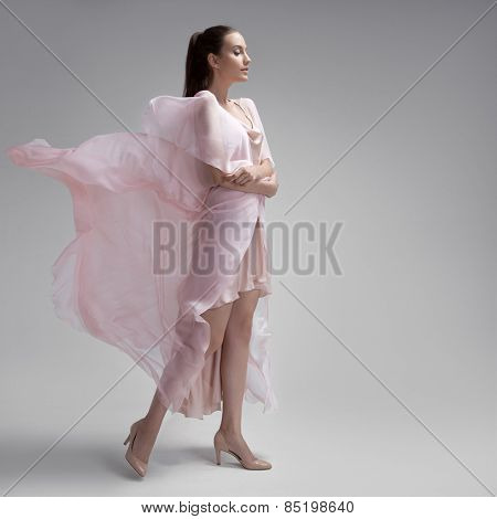 Beautiful woman in fluttering airy pink dress. Gray background.