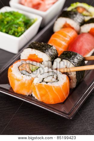 Delicious sushi rolls served on black plate and stone poster