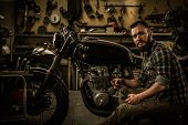 Mechanic building vintage style cafe-racer motorcycle  in custom garage poster
