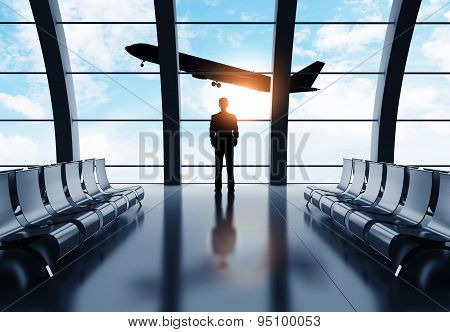 Man In Airport Looking On Airplane
