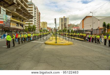 Quito city street closed off by long line police officers awaiting Pope Francis motorcade to arrive,