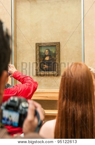 Group of tourists gathered around the Mona Lisa in the Louvre Museum.