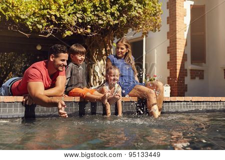 Happy Family Having Fun By The Swimming Pool