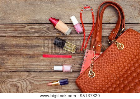 Things from open lady handbag. women's purse on wood background. Toned image.