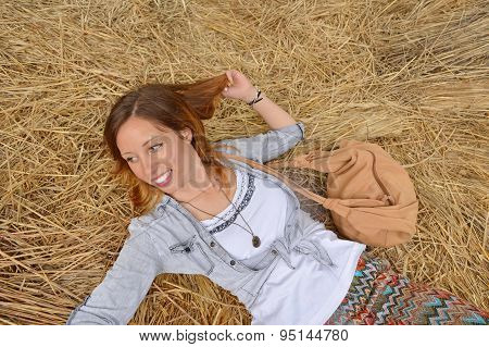 Happy Girl Lying On A Straw Pile