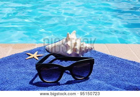 Poolside towel with sunglasses conch shell and starfish
