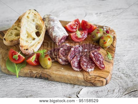 Delicious Appetizers For Wine - Italian Sausage, Olives, Tomatoes And Ciabatta On Olive Board On A L