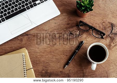Laptop With Notebook And Cup Of Coffee On Old Wooden Table