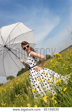 Rockabilly Or Pin Up Girl With A Petticoat Dress And A Umbrella In A Meadow