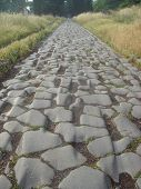 an ancient wheel-worn stone road. traces of centuries gone by. poster